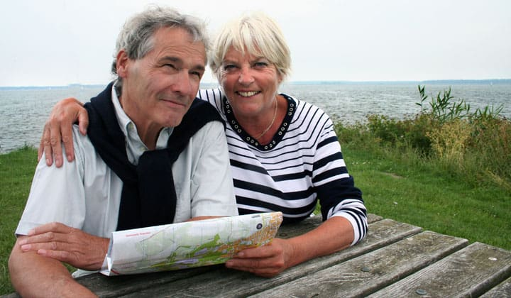 Elderly couple sitting at a park bench reading a map with ocean in the background